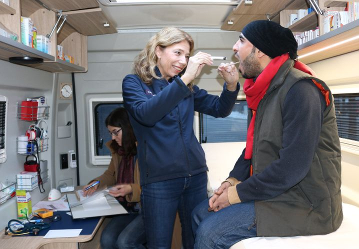 A doctor with a mobile clinic provides care to a refugee in the city of Tübingen. Most refugees are initially excluded by law from anything but urgent care.