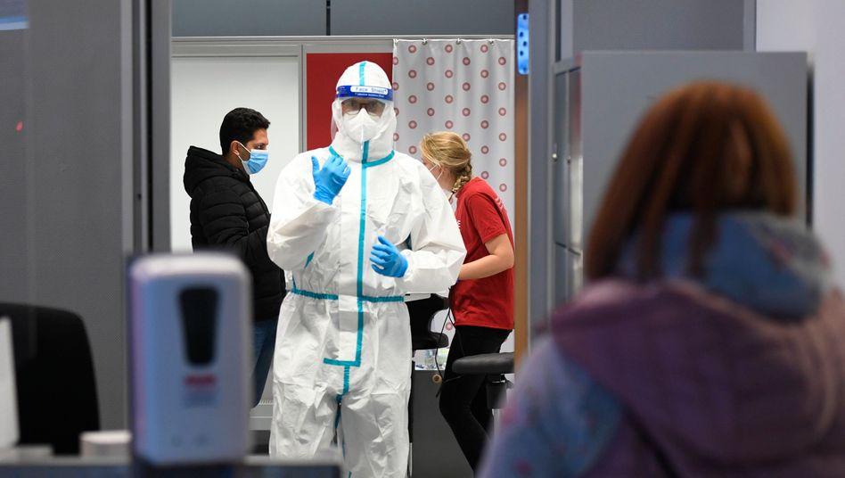 Am Düsseldorfer Flughafen wartet ein Mitarbeiter einer Biotechnologiefirma auf Kunden, die sich auf das Coronavirus testen lassen wollen