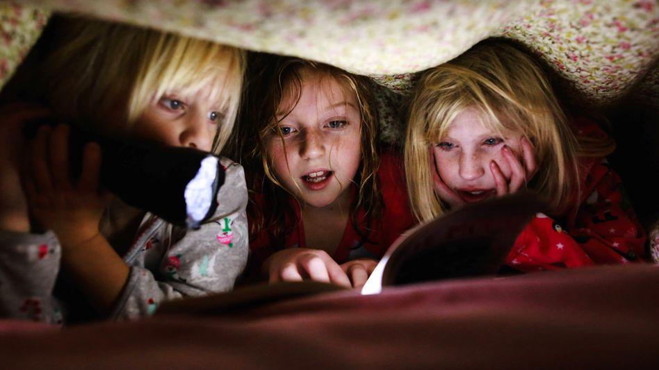 Mit Geschwistern, unter der Bettdecke und mit einer Taschenlampe zur Beleuchtung - so wird ein Buch gleich doppelt spannend