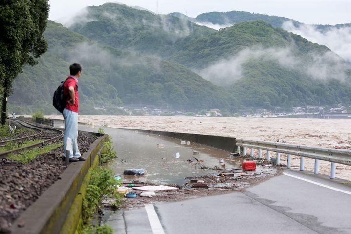 Ein Mann blickt auf den überfluteten Fluss Kuma in der Provinz Kumamoto.
