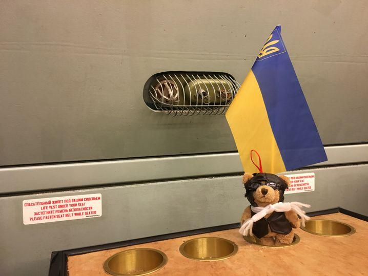 In der Kabine steht ein Berliner ILA-Bär vor einer ukrainischen Fahne