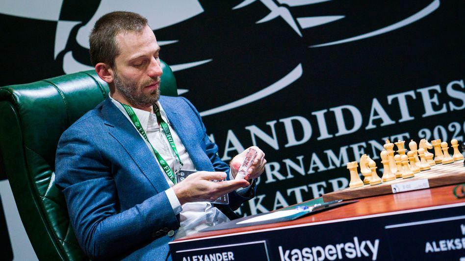 Der russische Schachspieler Alexander Grischuk desinfiziert seine Hände am Schachbrett in Jekaterinburg