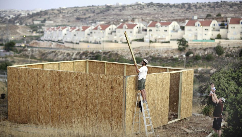 Jewish settlers build a hut near their home in a small outpost near the settlement of Kiryat Arba next to the West Bank city of Hebron.