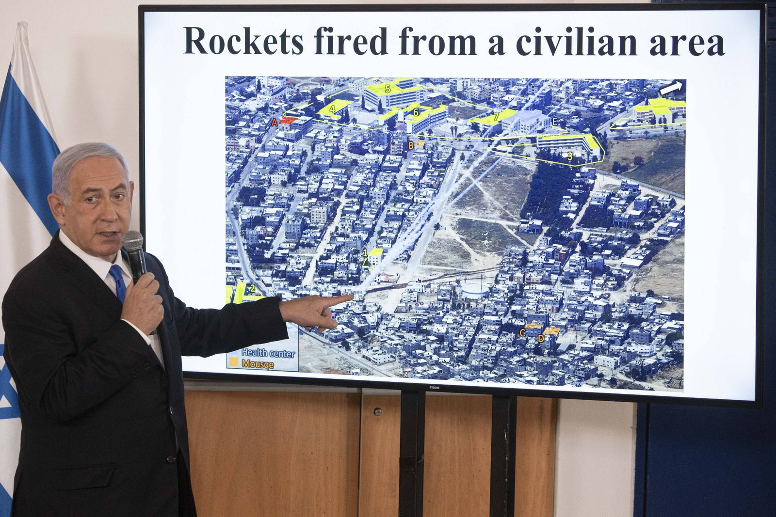 Israeli Prime Minister Benjamin Netanyahu gestures as he shows a slideshow during a briefing to ambassadors to Israel, a