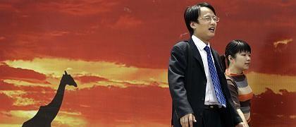 Anzugträger vor Werbeplakat (in Peking): Die chinesische Führung ermuntert Büroarbeiter, künftig T-Shirts zu tragen - und die Klimaanlagen herunterzudrehen