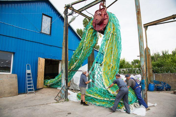 Ein fertiges, Tonnen schweres Trawl-Netz wird aus der Werkshalle gezogen. Die Netze werden immer größer und damit schwerer.