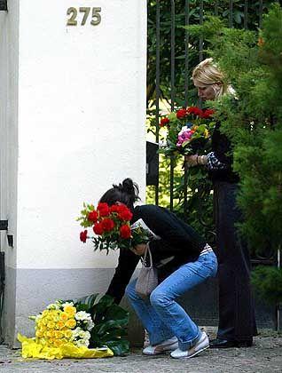 Zwei junge Mädchen legen vor der Wohnung des entführten Jungen Blumen nieder