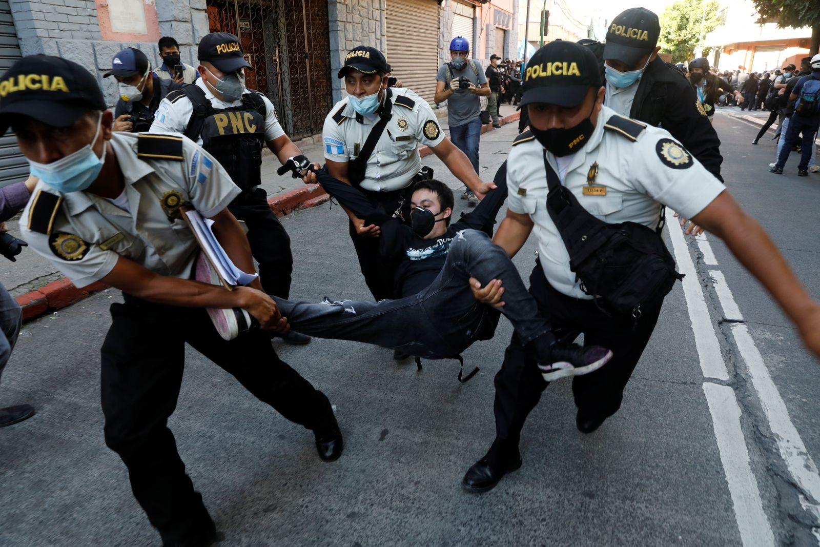 Police officers carry a demonstrator taking part in a protest demanding the resignation of President Alejandro Giammattei, in Guatemala City