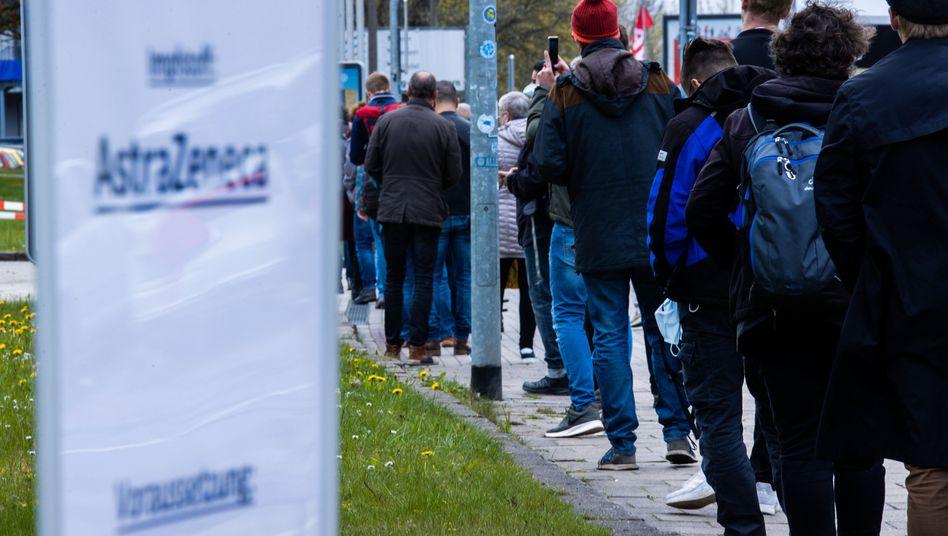Menschen stehen vor einem Impfzentrum in Schwerin Schlange