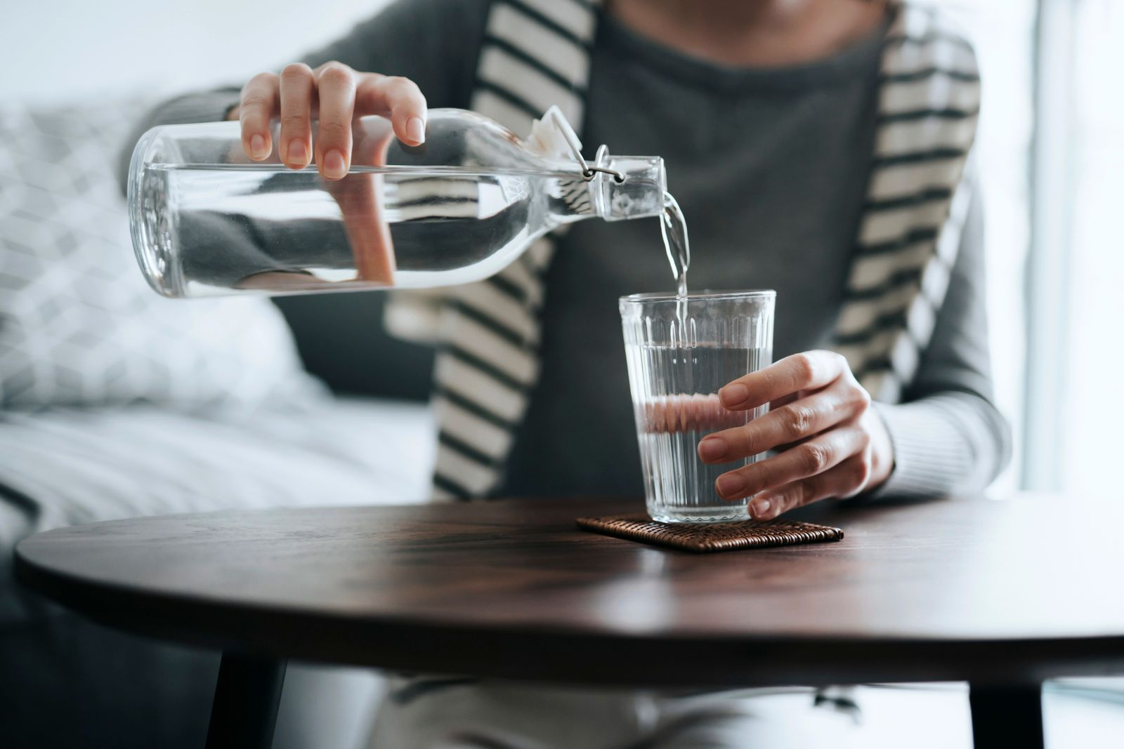 Close up of young Asian woman pouring water from bottle into the glass on a coffee table at home. Healthy lifestyle and stay hydrated