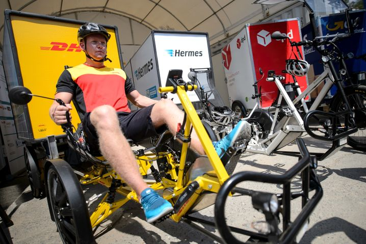 A DHL employee uses a cargo bike to deliver packages in Berlin.