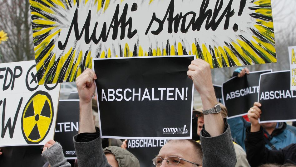 """In Germany, """"Mutti,"""" or """"mother,"""" is a name often used in Berlin political circles in reference to Chancellor Angela Merkel. A protester's sign reads: """"Mutti is emitting radiation."""" The others read: """"Turn them off!"""""""