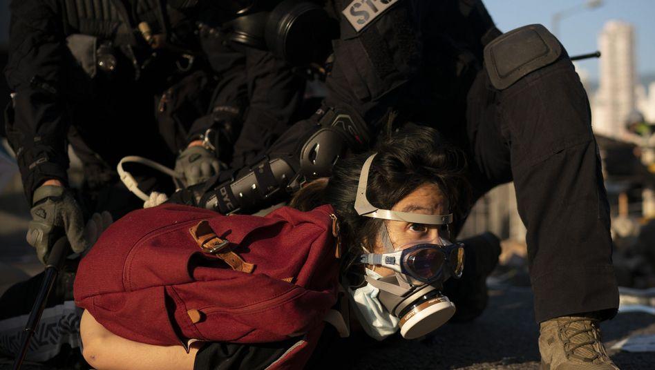 Auf dem Boden liegend festgenommen: Demonstrantin in Hongkong
