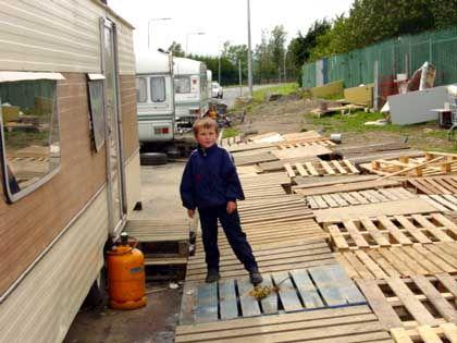 Holzplanken liegen auf dem Boden vor den Caravans der Mongans