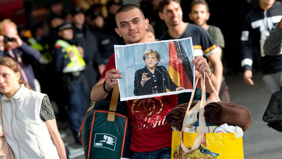 5. September 2015: Ein Flüchtling, der kurz zuvor in Deutschland angekommen ist, hält ein Foto von Angela Merkel in den Händen