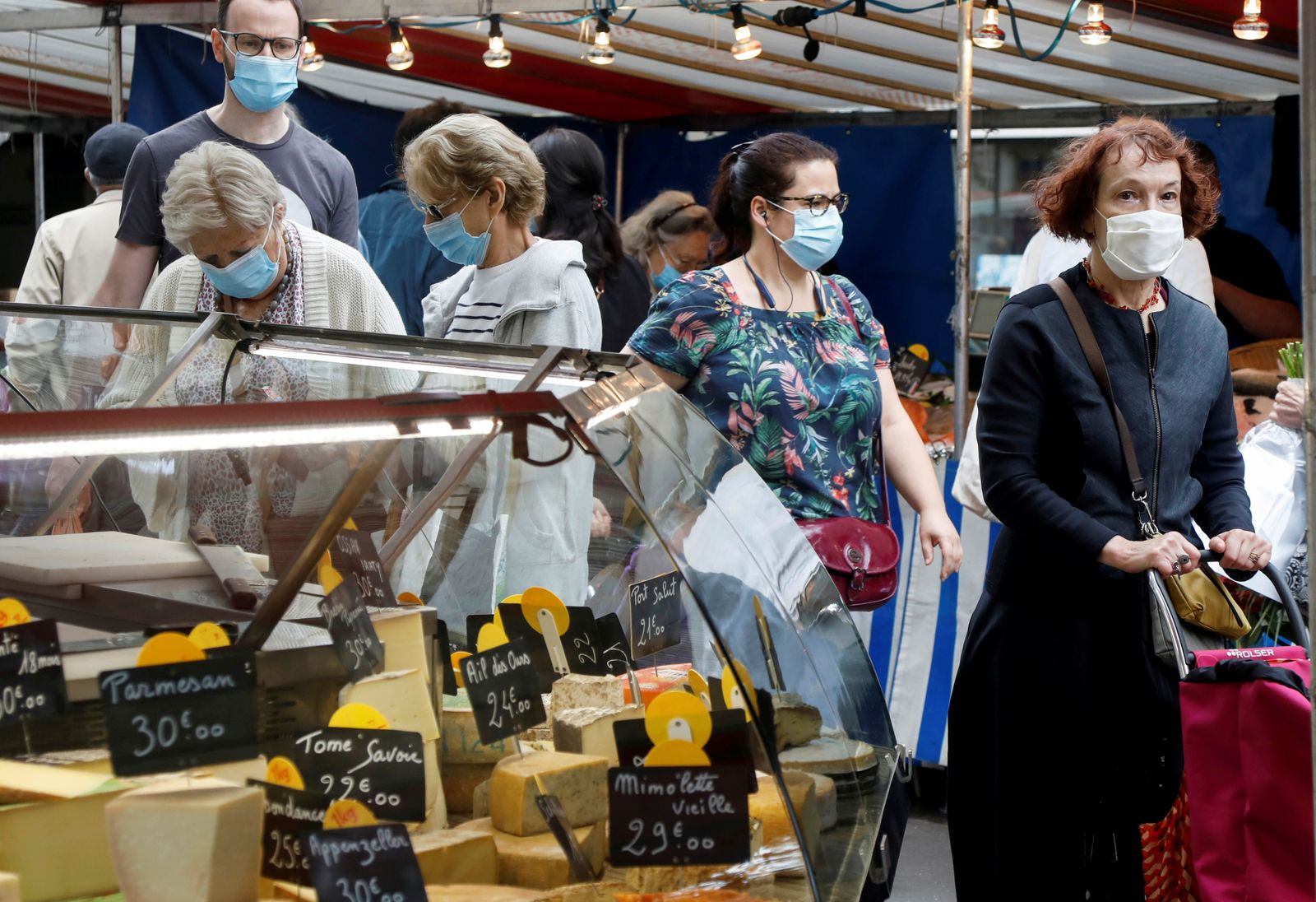 FILE PHOTO: People wear protective masks at an open-air market, in Paris