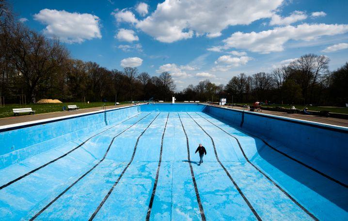 Mann bei Instandhaltungsmaßnahme im leeren Schwimmbecken des Freibads Kleefelder Bad-Annabad