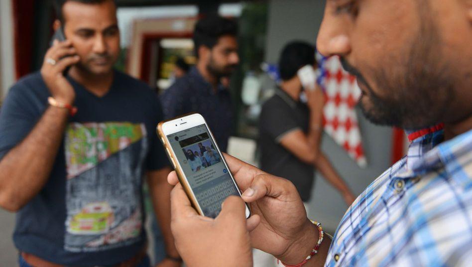 Indische Männer an Smartphones (Archivbild): Immer wieder wird in einzelnen Gegenden das Internet abgeschaltet