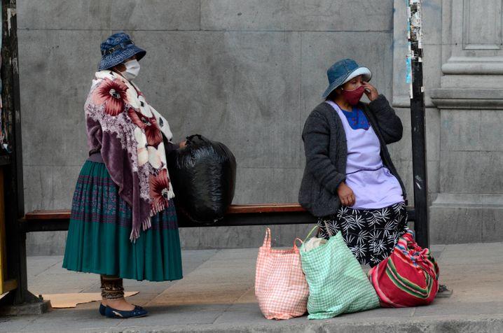 Frauen mit Mundschutz in La Paz: Die Masken mit dem Parteilogo waren schon gedruckt