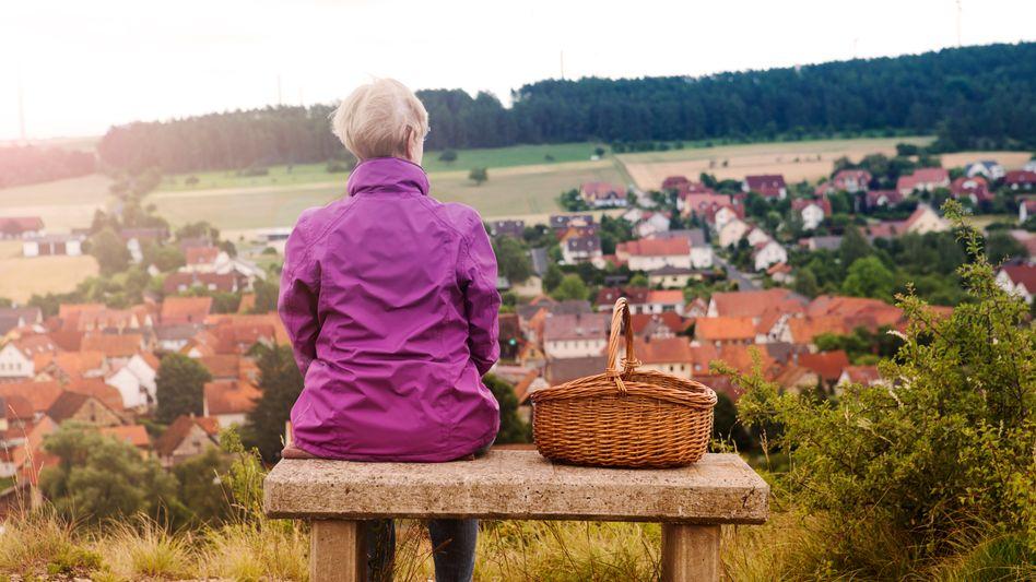 Ältere Frau auf einer Bank mit Blick über eine Kleinstadt