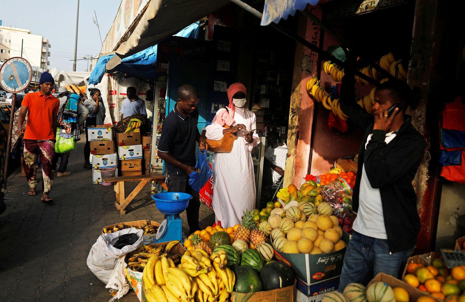A woman wears a face mask, due to the global coronavirus disease (COVID-19) outbreak, as she shops along a busy shopping street in Dakar,