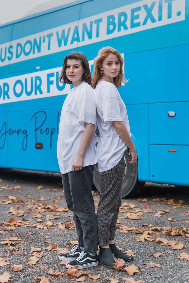 Lucy Swale and Matilda Allan pose in front of the blue bus.