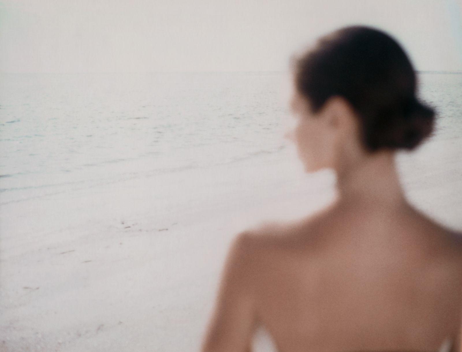 Woman on beach, rear view, defocused