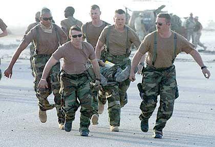 Eilige Hilfe: Soldaten im Südirak transportieren einen verwundeten US-Marine auf einer Trage. Er und andere Verletzte wurden zur Behandlung zunächst nach Kuweit gebracht.