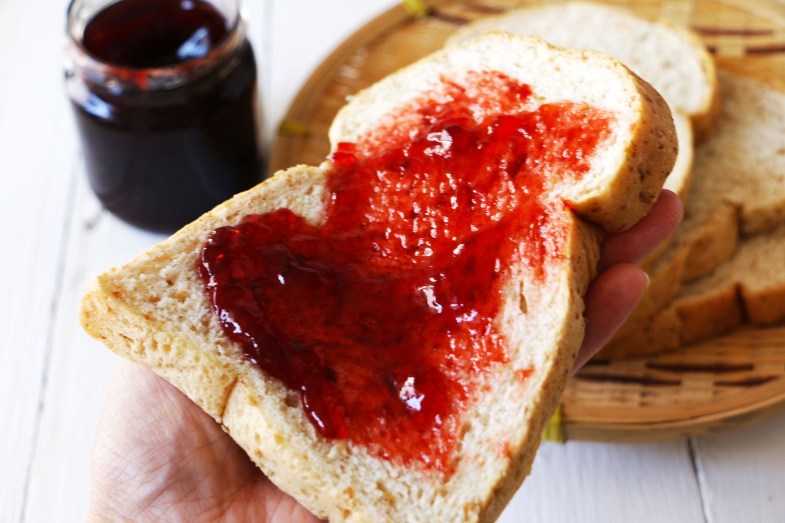 Cropped hand holding bread with jam