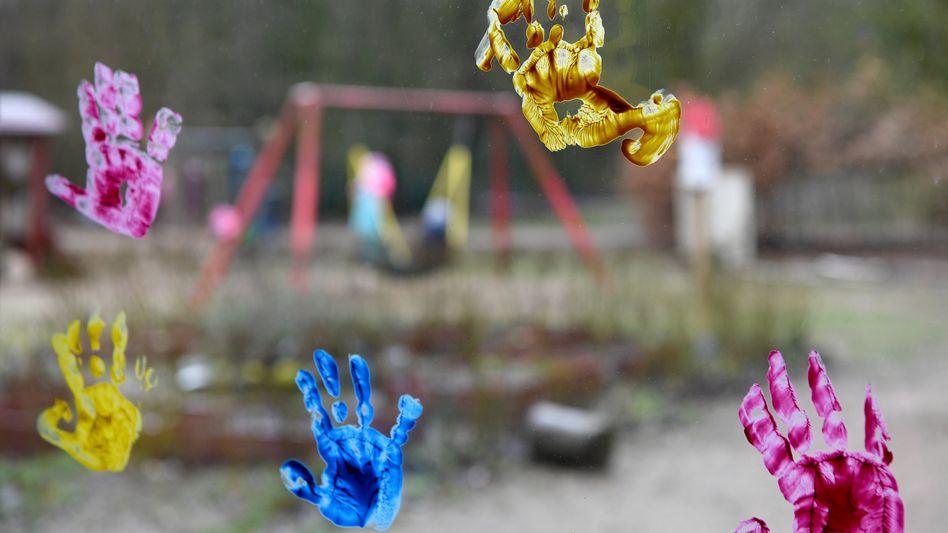 Abdrücke von Kinderhänden an Fensterscheibe zum Spielplatz: Kitas bleiben in der Coronakrise weiter geschlossen