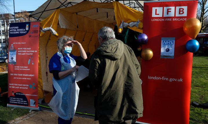 Eine Ärztin des »Vaxi Taxi«-Teams informiert einen Patienten vor dem Impfzelt in Kilburn, im Süden des Londoner Stadtteils Brent