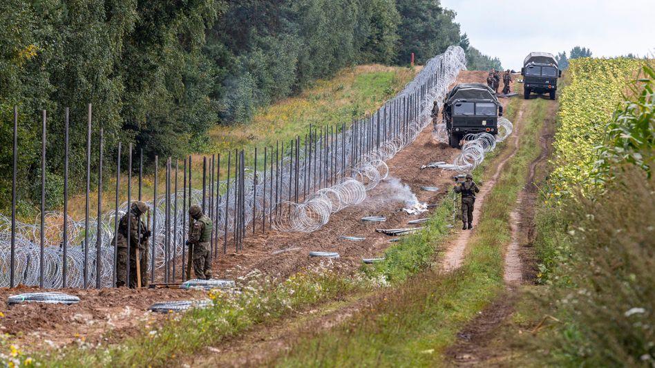 Polnische Soldaten errichten einen Grenzzaun, um Migranten aus Belarus zu stoppen