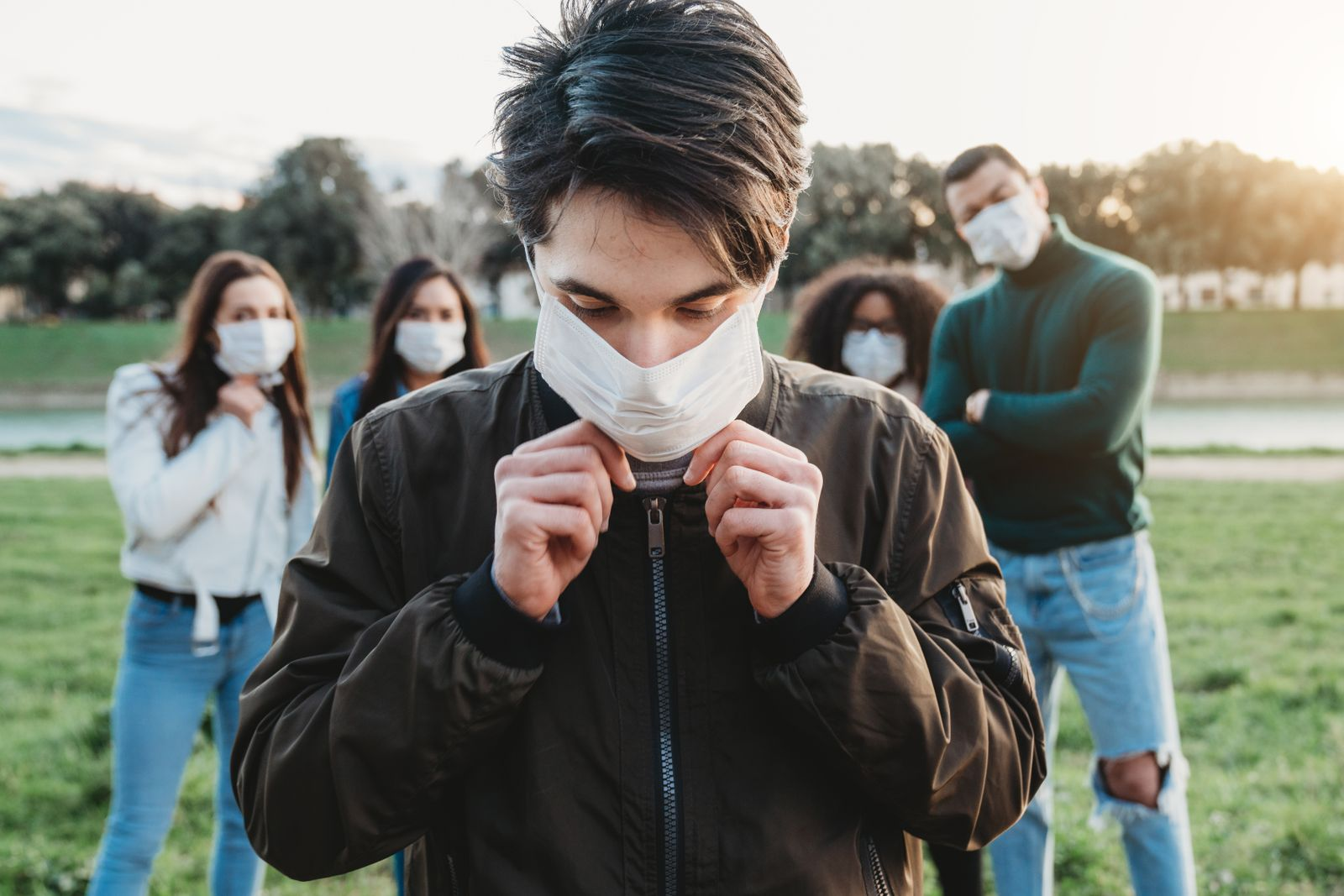 Young adult man wearing a pollution mask to protect himself from viruses. His friends are in the background.