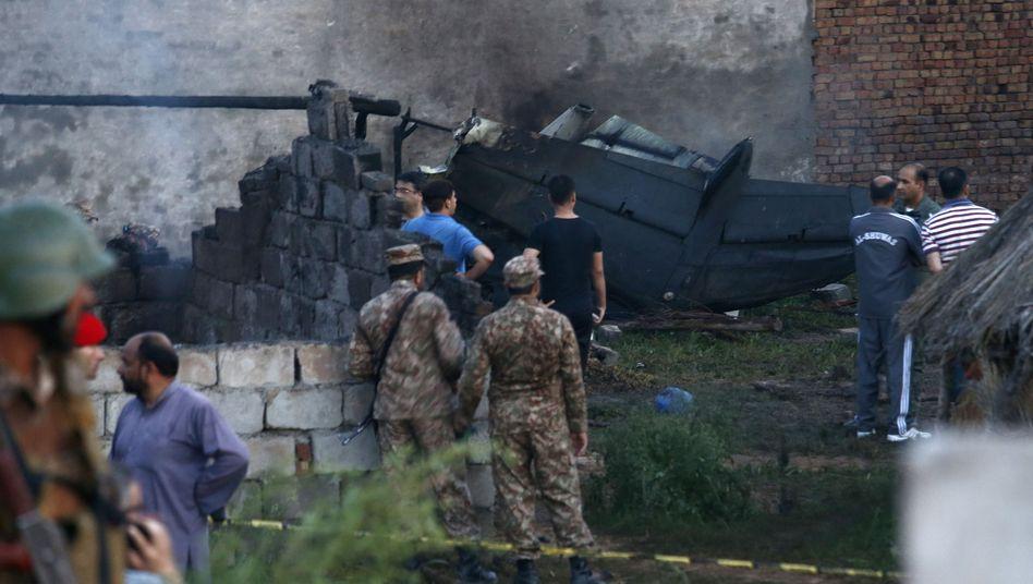 Mitarbeiter des Militärs untersuchen den Ort des Flugzeugabsturzes