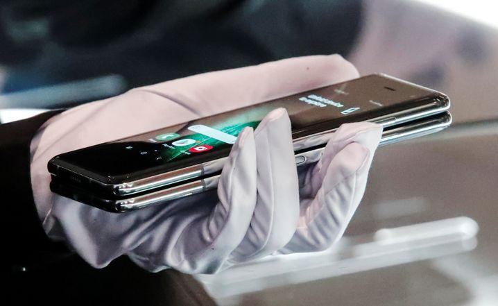 Ein Samsung-Mitarbeiter präsentiert das Galaxy Fold 5G mit Schutzhandschuhen, damit darauf kein Fingerschmutz haften bleibt