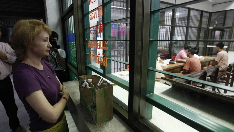 Alla Bout brings a bag of food for her husband at the criminal court in Bangkok, Thailand.