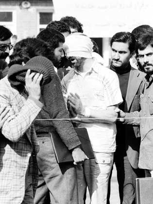 Blindfolded and with his hands bound, an American hostage is led by young militants to a mob in front of the US Embassy in Tehran, Iran in November 1979.