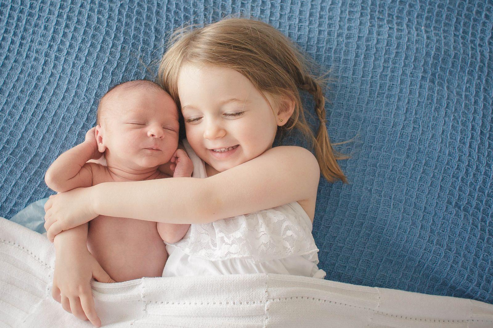 Preschool Girl Hugs Newborn Baby Brother