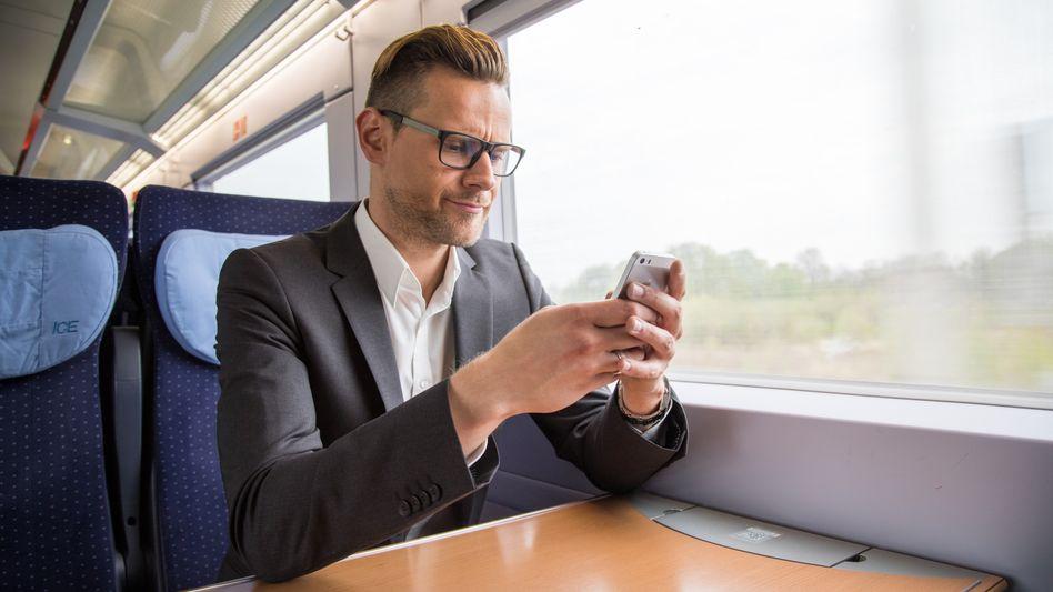 Bahnfahrer mit Smartphone