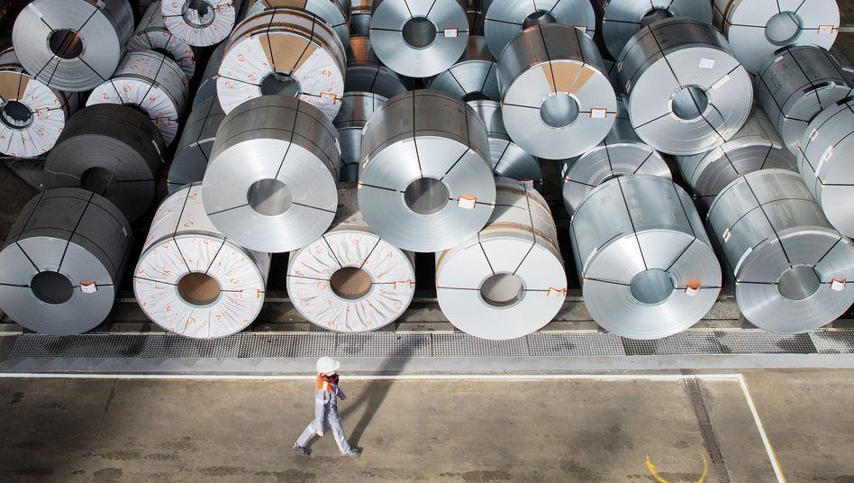 Eine Mitarbeiterin geht auf dem Gelände der Salzgitter AG an sogenannten Stahlcoils entlang