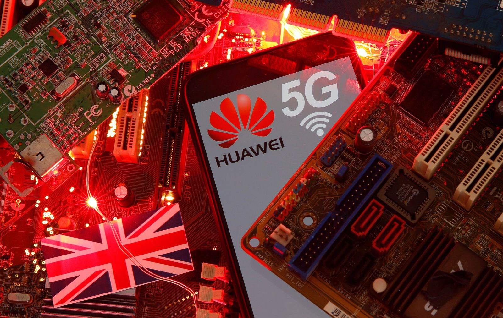 The British flag and a smartphone with a Huawei and 5G network logo are seen on a PC motherboard in this illustration