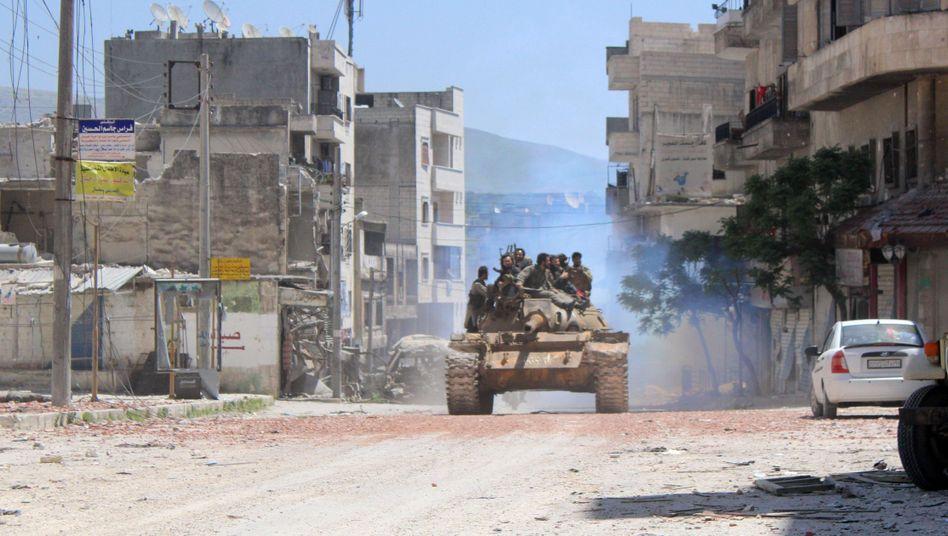 Umkämpfte Stadt Dschisr al-Schughur (im April): Rebellenkämpfer fahren mit einem Panzer durch die Stadt