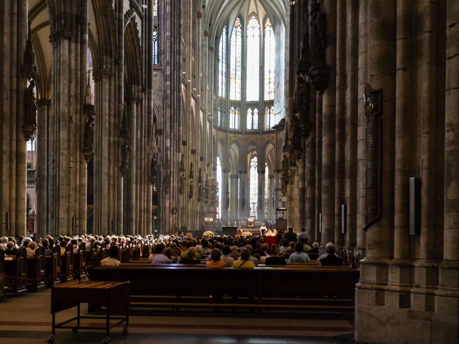 visitors in church service in Cologne Cathedral