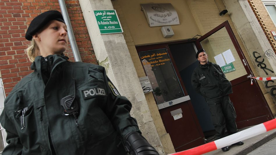 Police officers outside an Islamic cultural center in Berlin following the arrest of two terror suspects.
