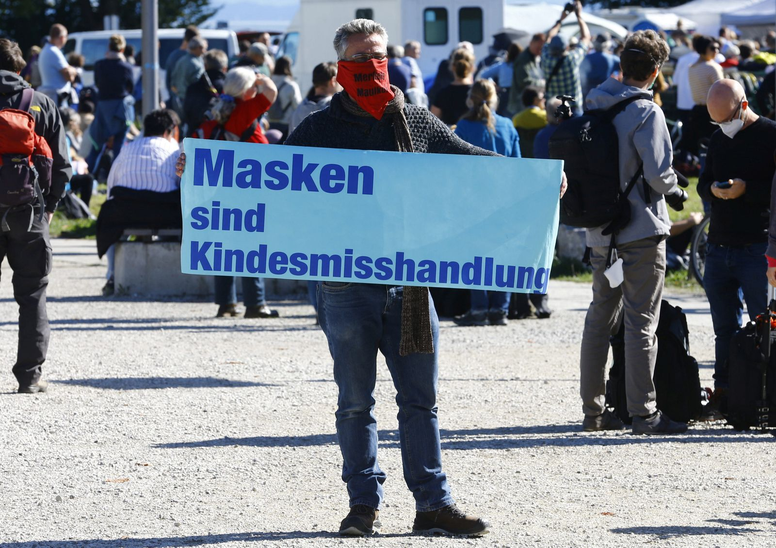 Man displays a poster during a protest against the government's restrictions in Konstanz