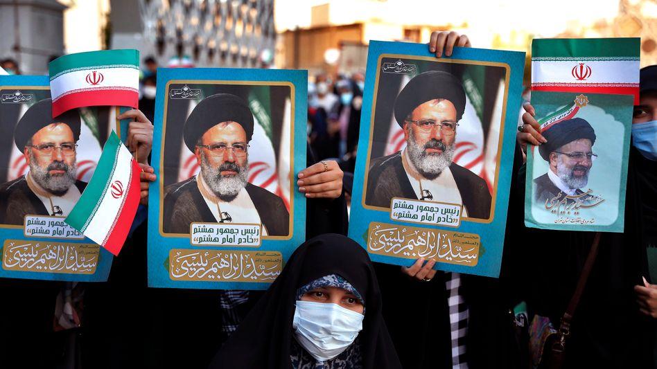 Raisi-Unterstützer mit Porträts des neu gewählten Präsidenten auf den Straßen in Teheran
