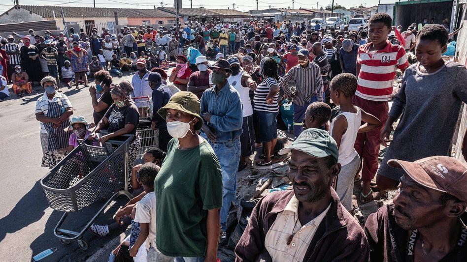Wartende vor einer Essensausgabe in der südafrikanischen Township Gugulethu