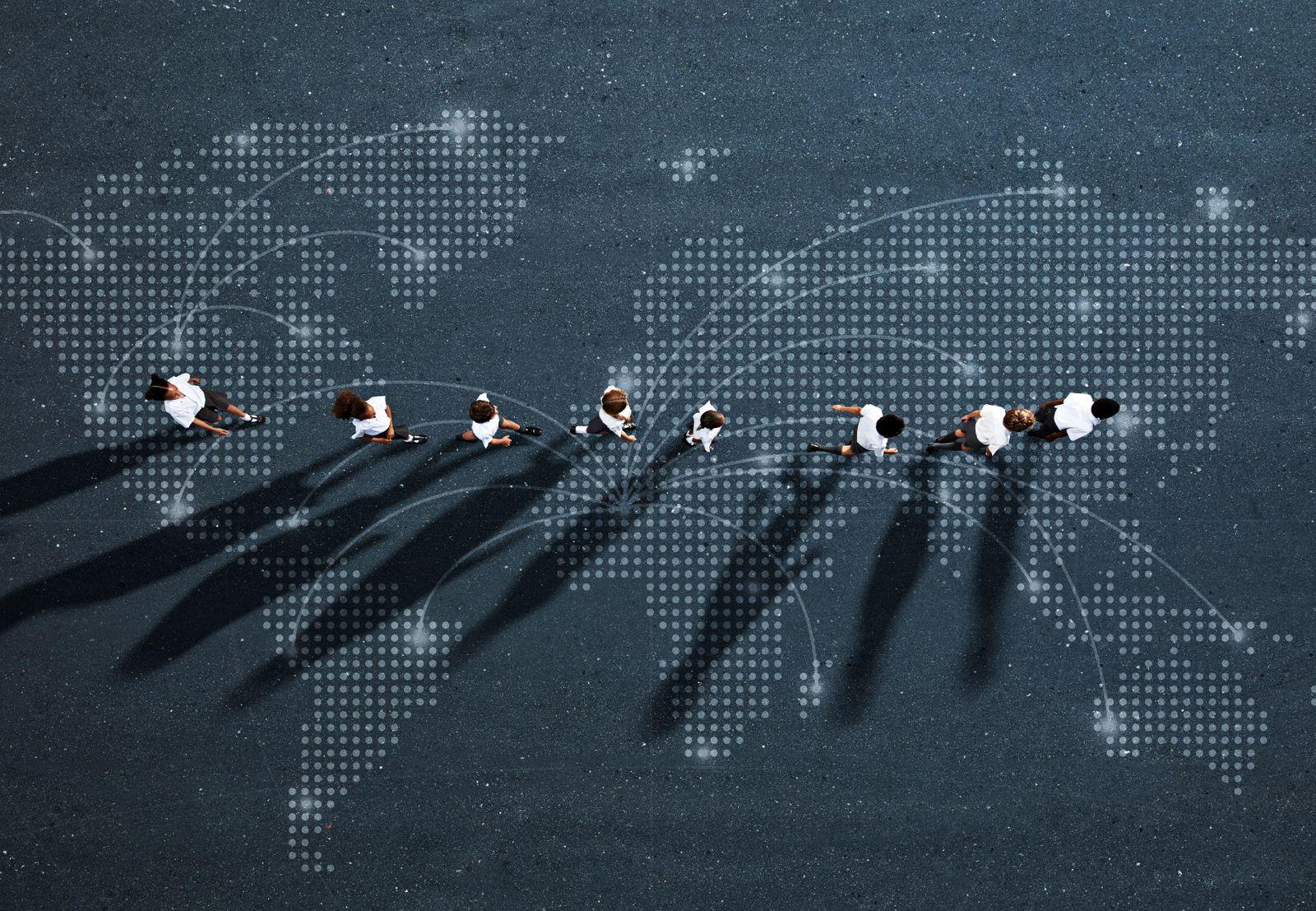 School children in uniforms walking in row across world map