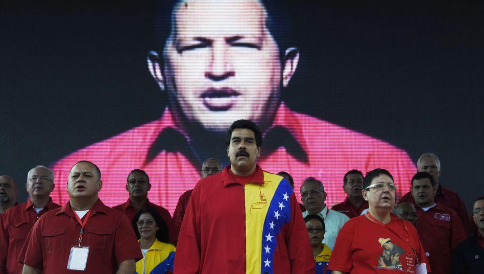 Nicolás Maduro vor einem Bildschirm, auf dem Hugo Chávez zu sehen ist (2014)