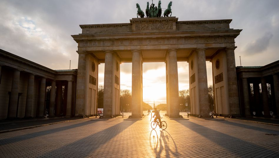 A lone cyclist in front of the Brandenburg Gate in Berlin: When can lockdown measures be loosened?